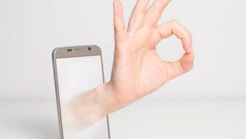 Hand kommt aus Handy