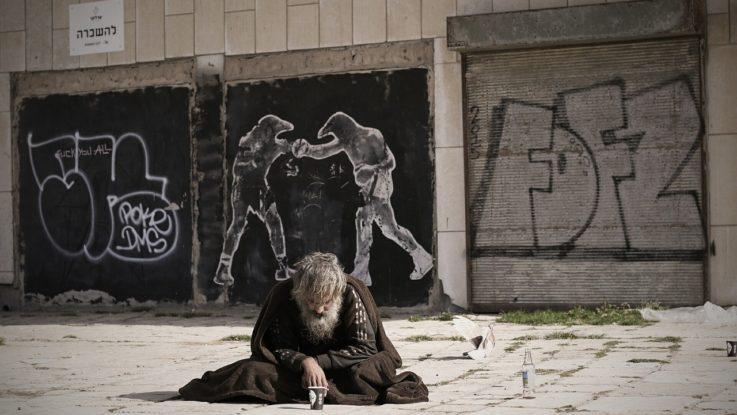 Obdachoser vor Wand mit Graffiti